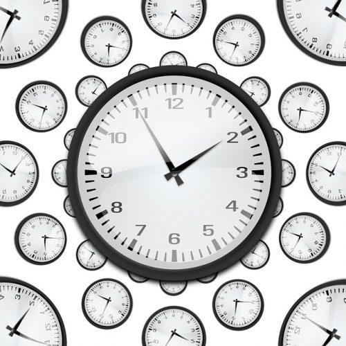 Uhr mit Zeigern und vielen Uhren im HIntergrund