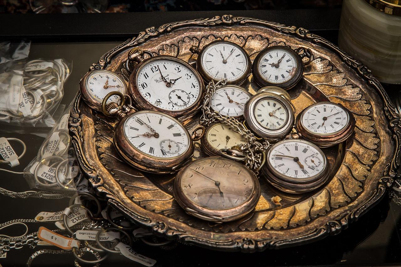 Viele Uhren in einer goldenen Schale zum Thema Zeitmanagement