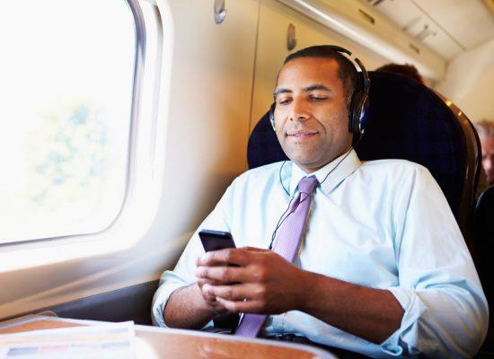 Business Mann sitzt in der Bahn und relaxed