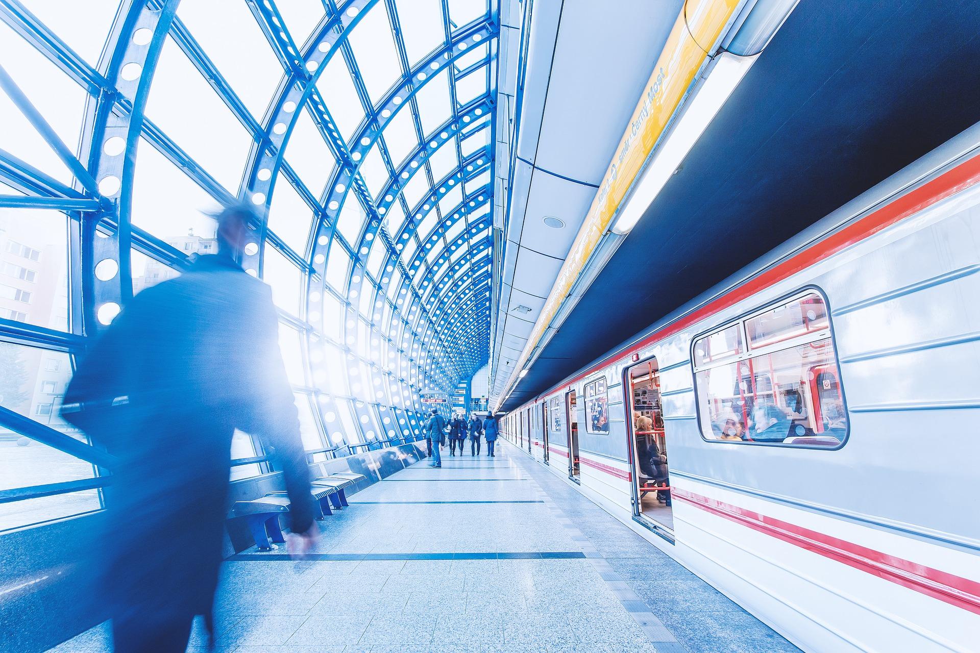 Stehender Zug mit offenen Türen an Bahngleis